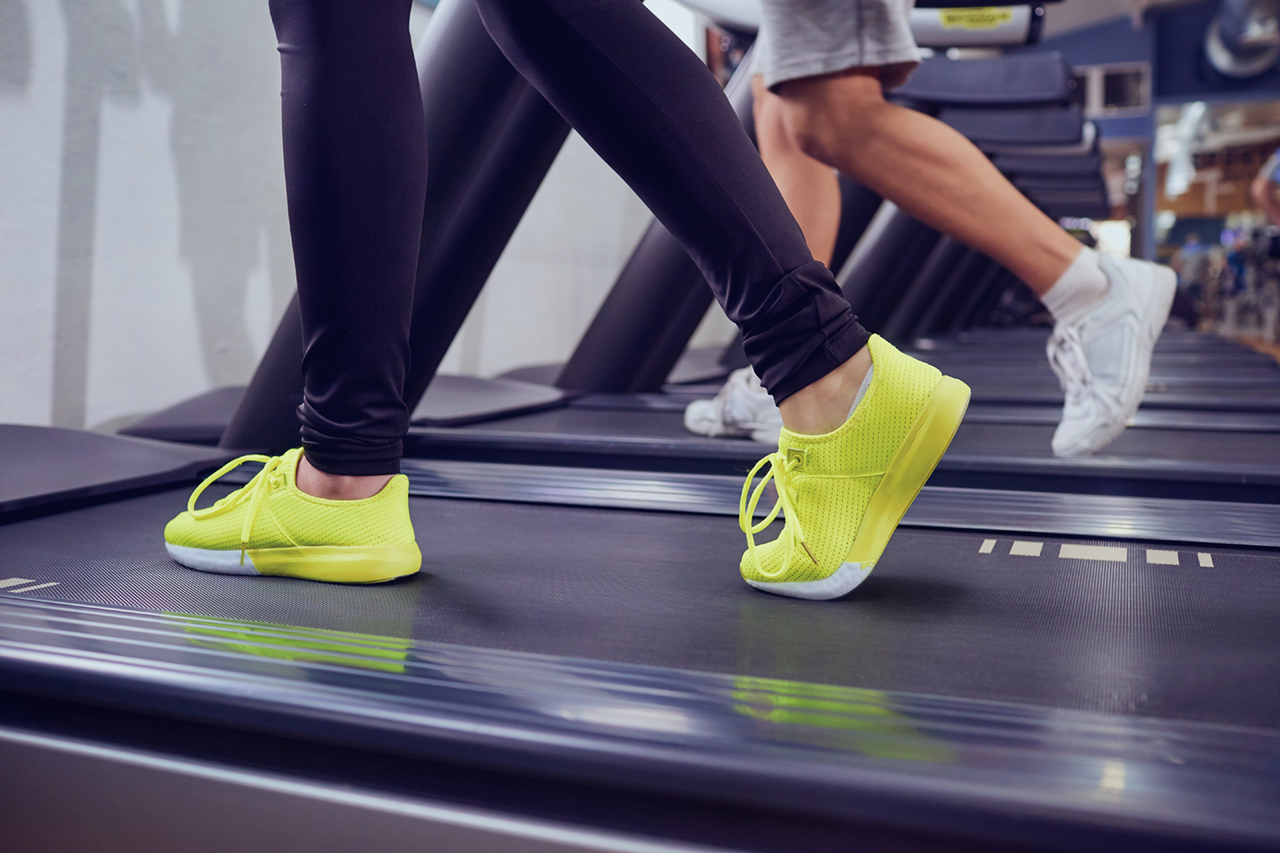 Detail of female legs on a treadmill in the gym